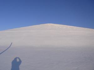 モエレ山南西斜面 斜面を横断しているトレースはスノーシューの跡.風が強く頂上付近は枯れ草が顔を覗かせている.